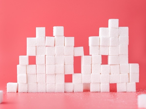 stacked white sugar cubes, with red background
